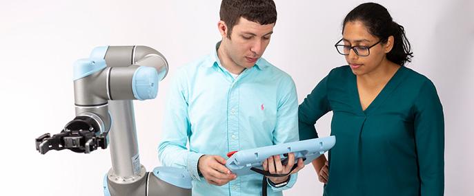Guru Subramani and Poragathi Praveena work with one of the Computer Sciences robots.