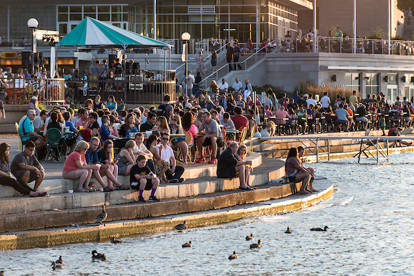People sitting along the curving cement steps that hug the Lake Mendota shoreline and Memorial Union Terrace as the sun sets on a summer evening.